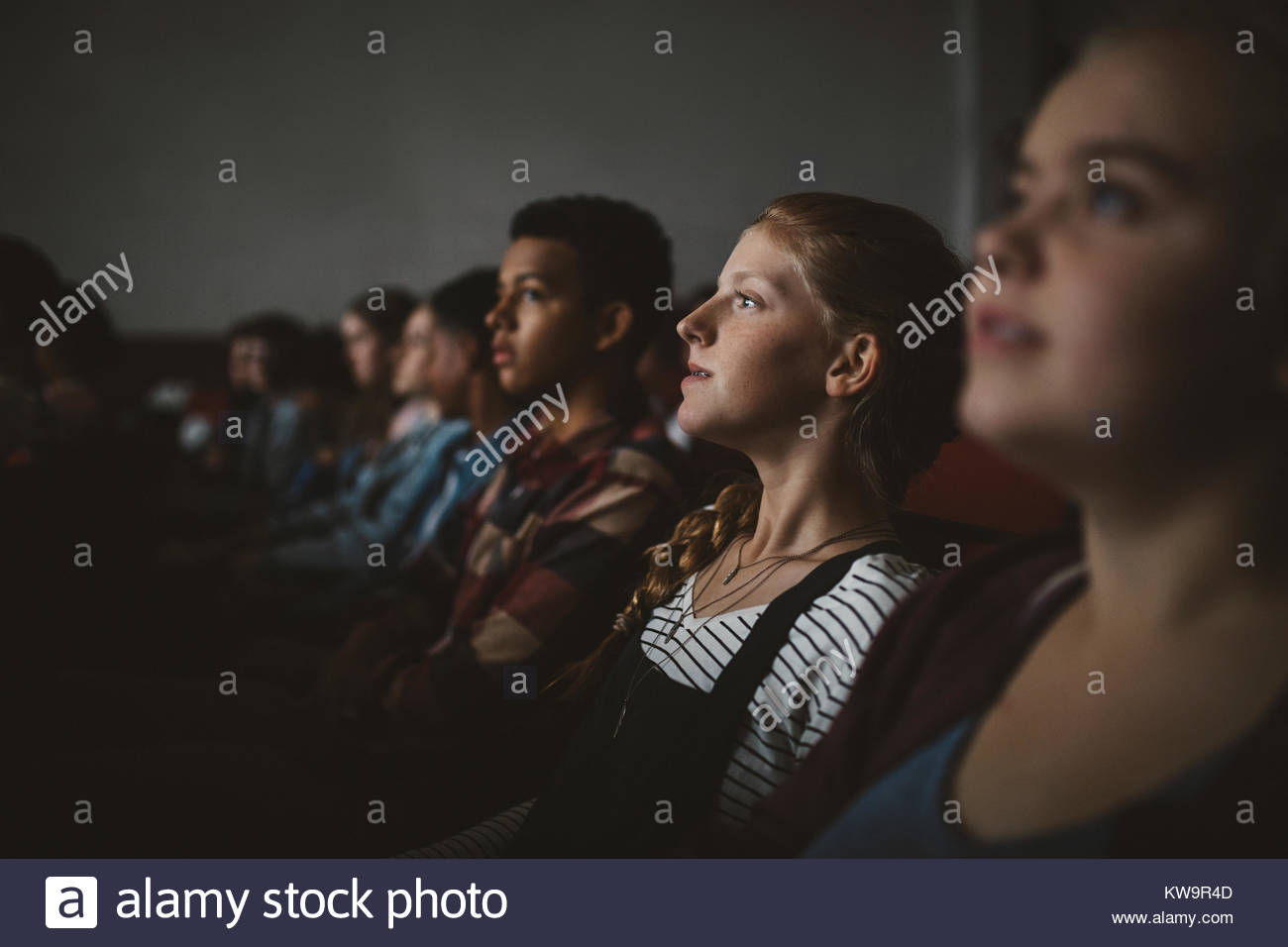 Ernsthafte tween Girl watching Film im dunklen Kino Stockbild