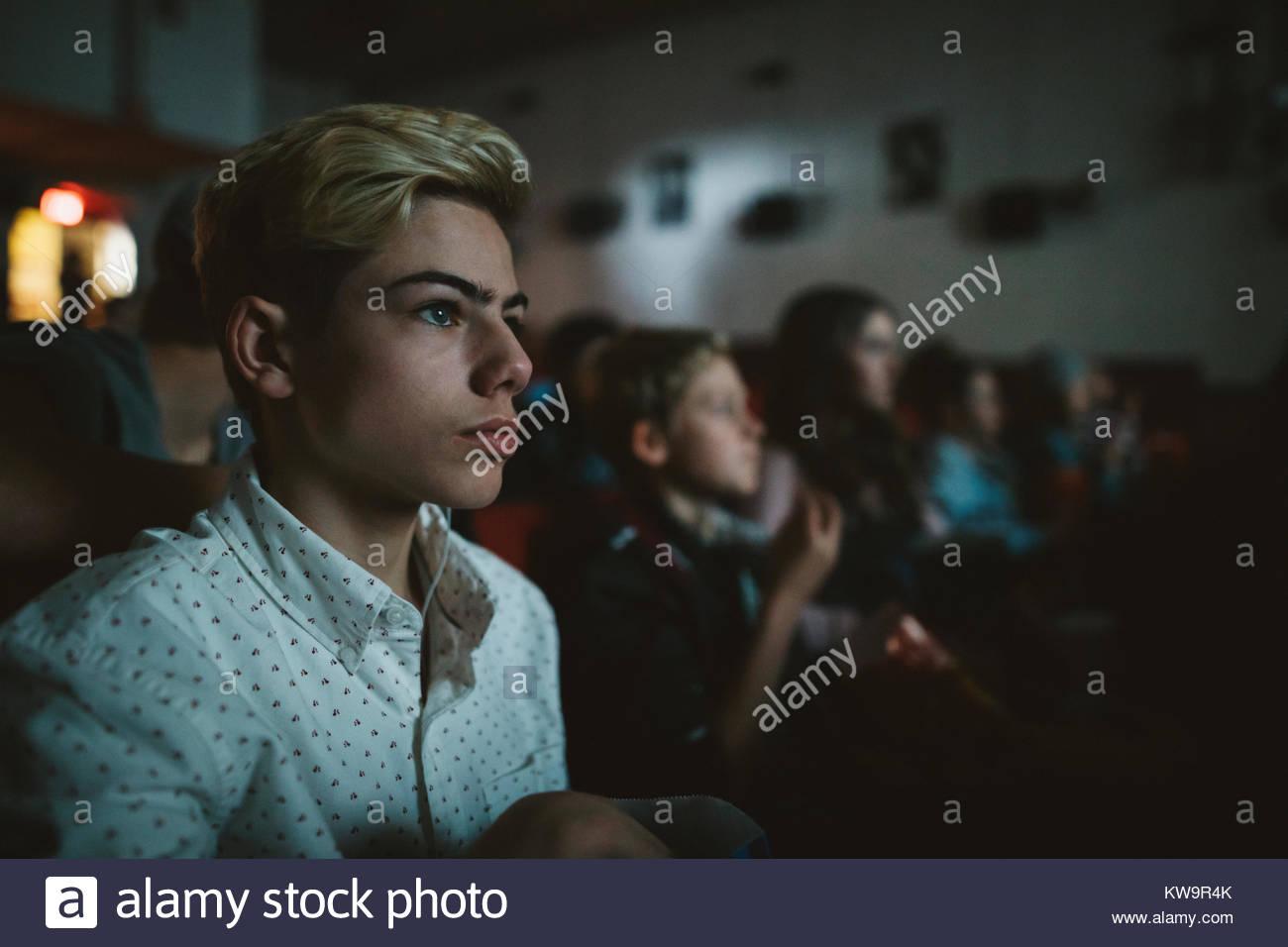Ernsthafte tween Boy watching Film im dunklen Kino Stockbild