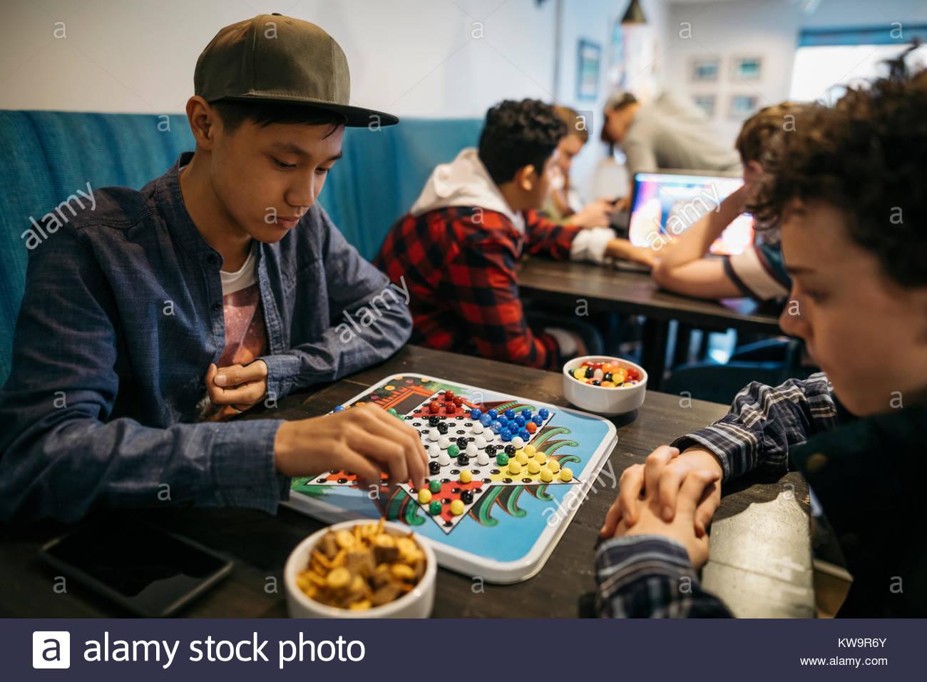 Tween junge Freunde spielen Chinese Checkers im Cafe Tabelle Stockbild