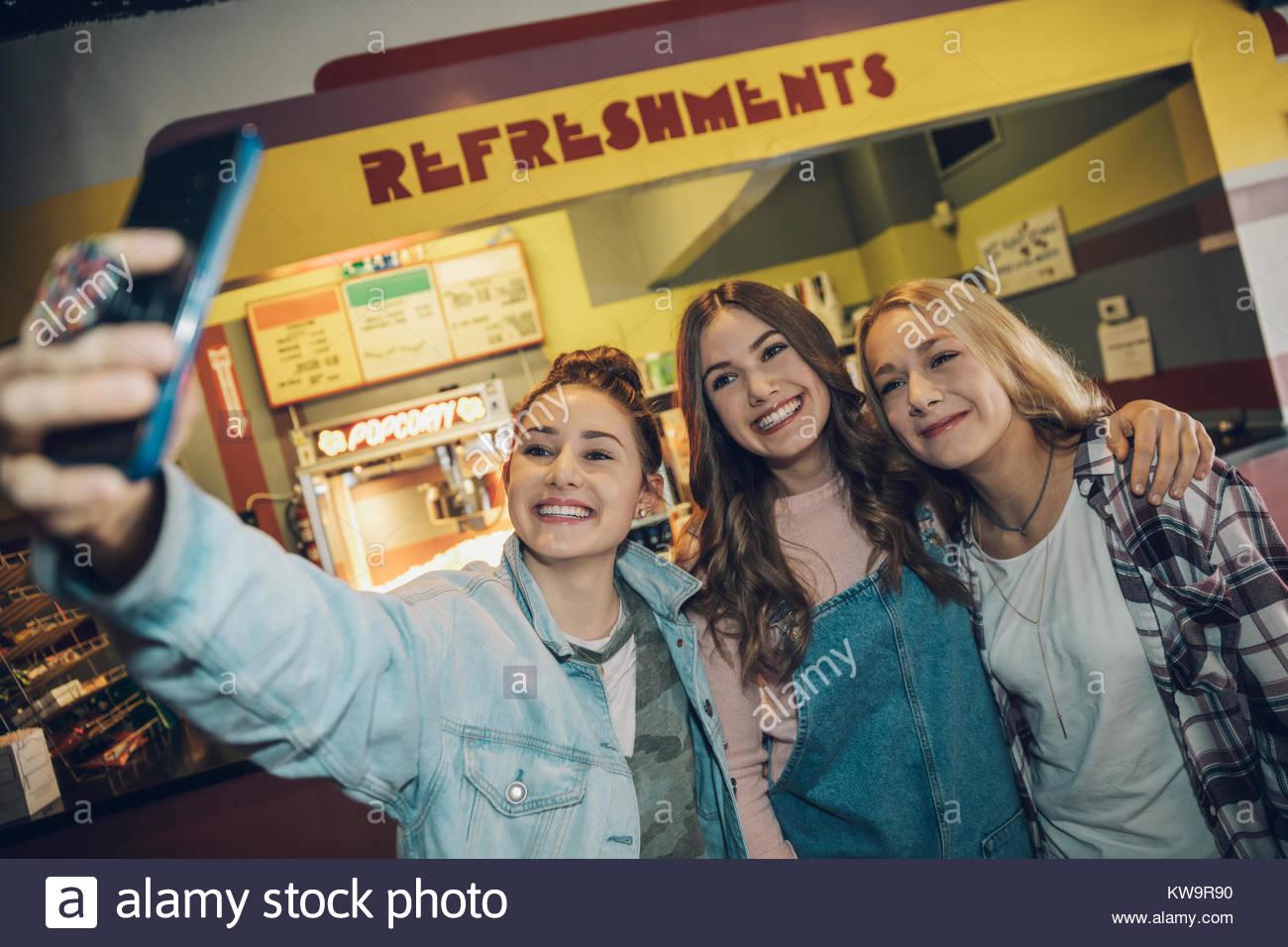 Lächelnd, enthusiastisch Kaukasischen tween girl friends unter selfie mit Kamera Handy im Kino Stockbild