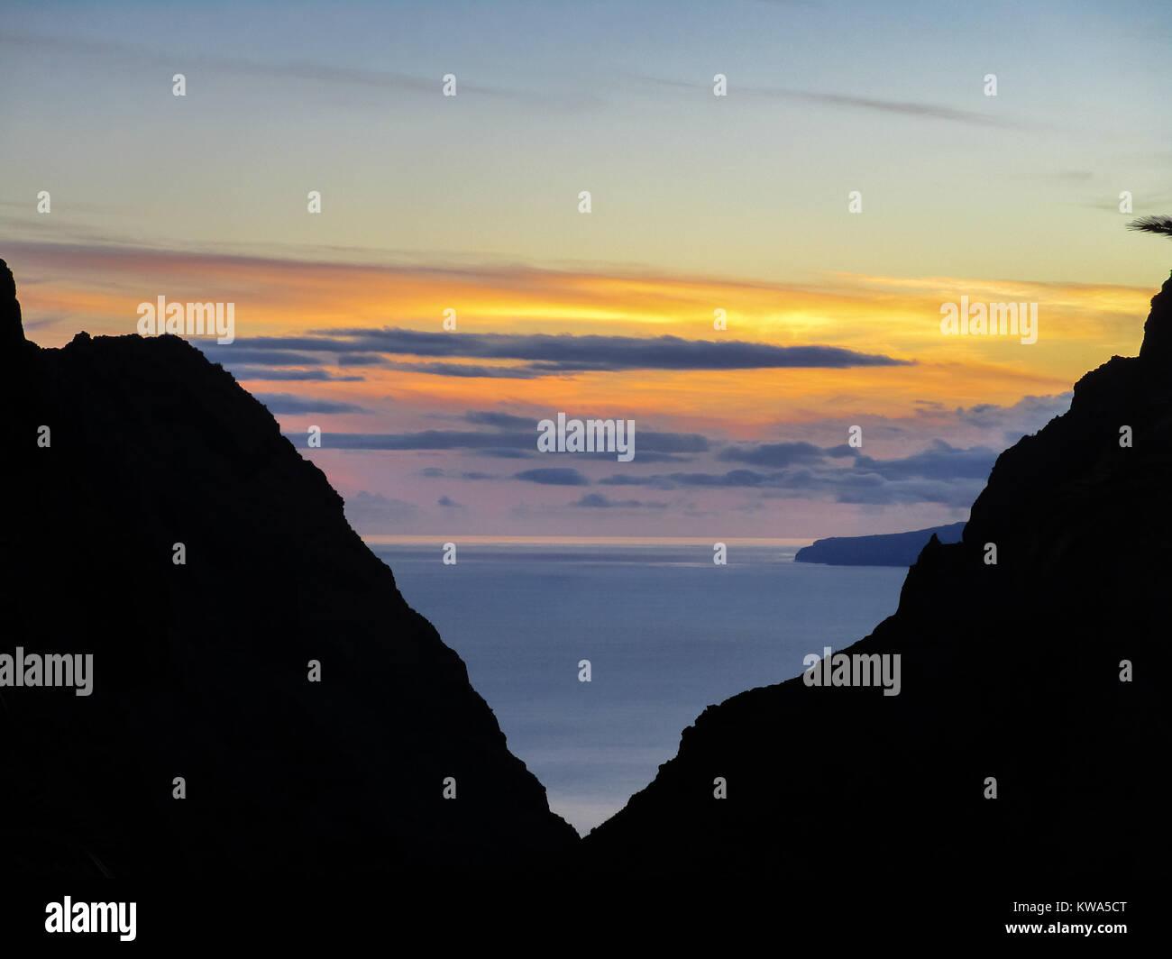 Berg Silhouette und Sonnenuntergang über dem Atlantischen Ozean, mit einem weit entfernten Teilweise mit Blick Stockbild