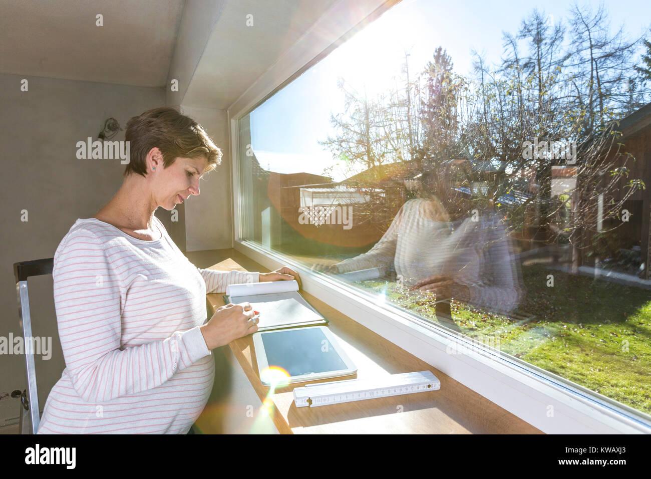 Schwangere Frau vor Fenster mit Unterlagen auf der Baustelle im neuen Haus Stockbild