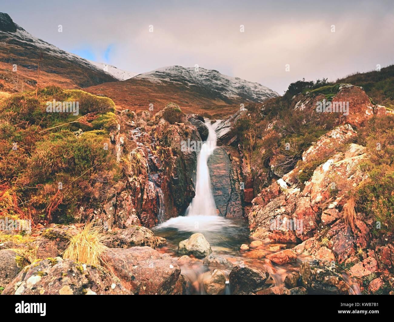 Berge Landschaft wildbach vor. Weiß verschneite Berggipfel und Grau bewölkter Himmel Stockbild