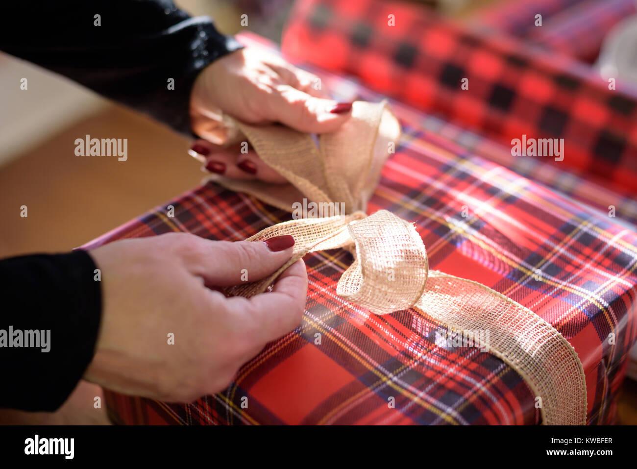 Nahaufnahme von Frau Verpackung Geschenk binden Schleife auf ...