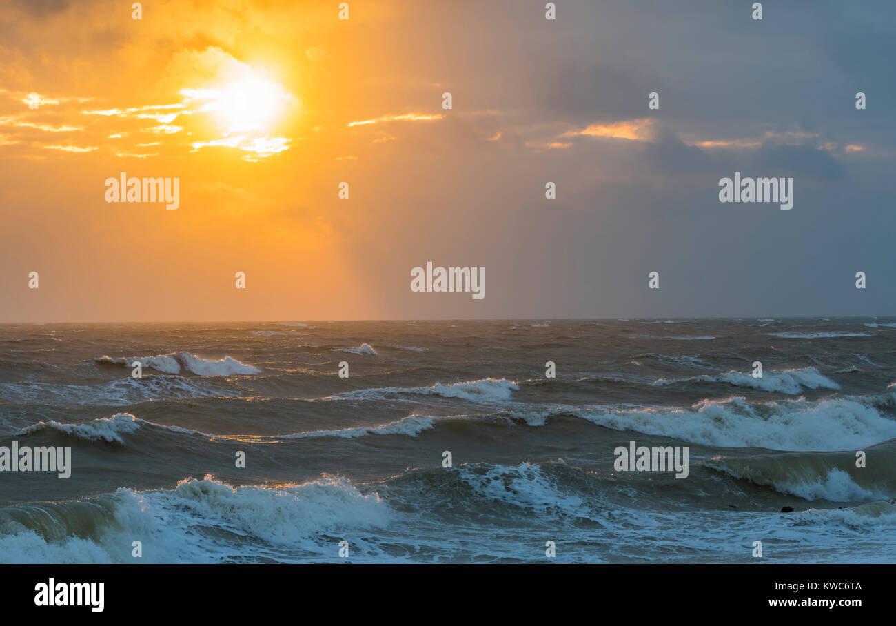 Niedrige Sonne teilweise verdeckt von Wolken über eine raue Meer im Winter. Stockbild