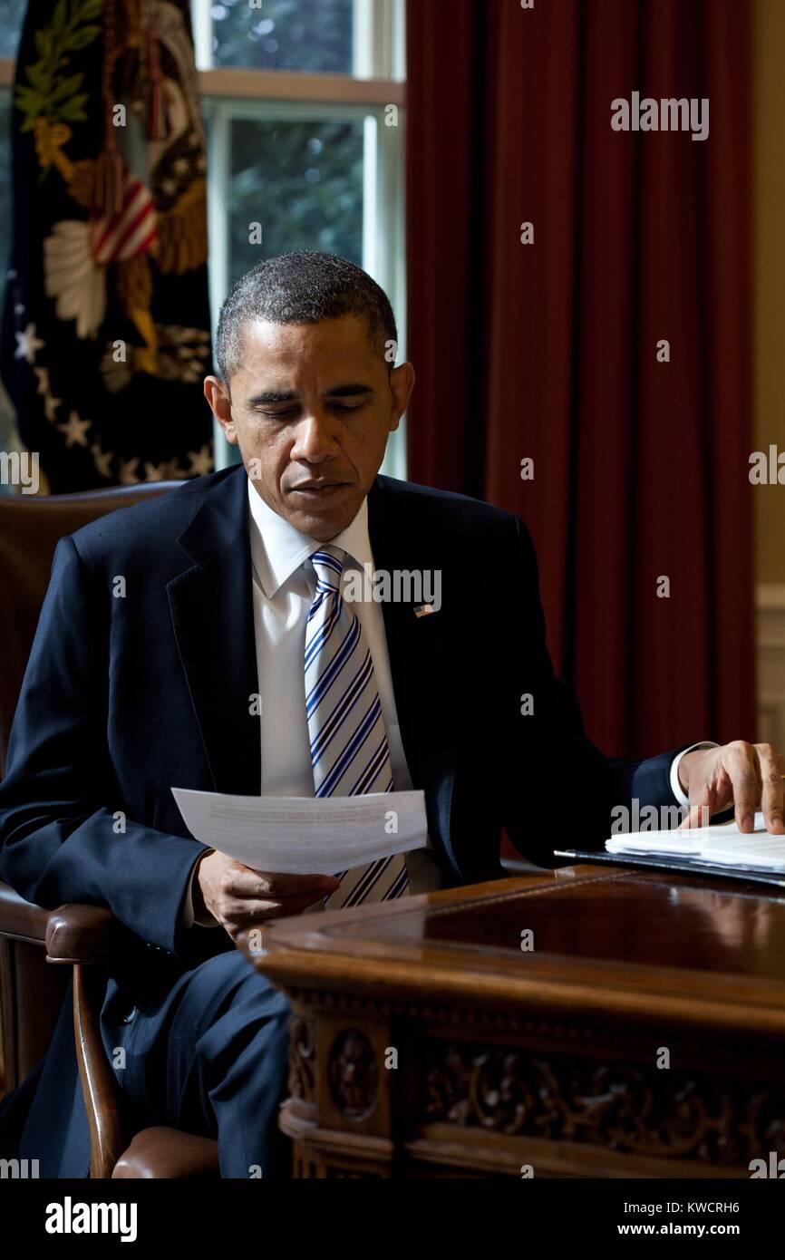 Präsident Barack Obama liest ein Dokument im Oval Office, 21. Februar 2012. (BSLOC_2015_3_3) Stockbild