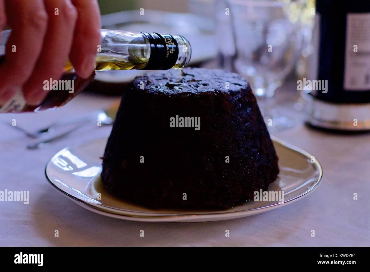 Des Menschen Hand gießen Brandy auf einem weihnachtspudding Stockfoto