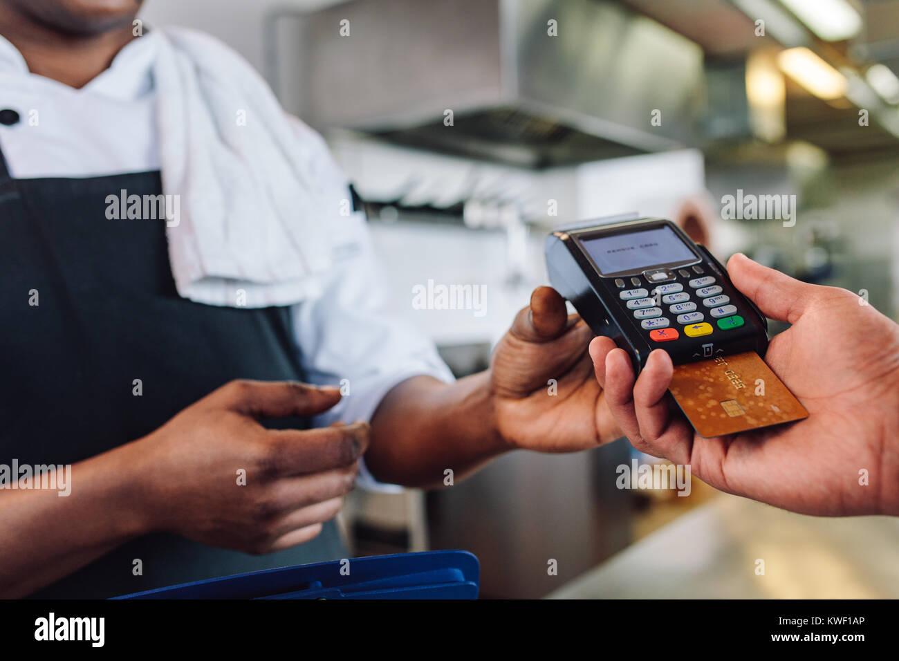 Der Kunde zahlt Restaurant Rechnung mit Kreditkarte. Kunden die Zahlung durch Kreditkarte am Zähler in einem Restaurant. Stockfoto