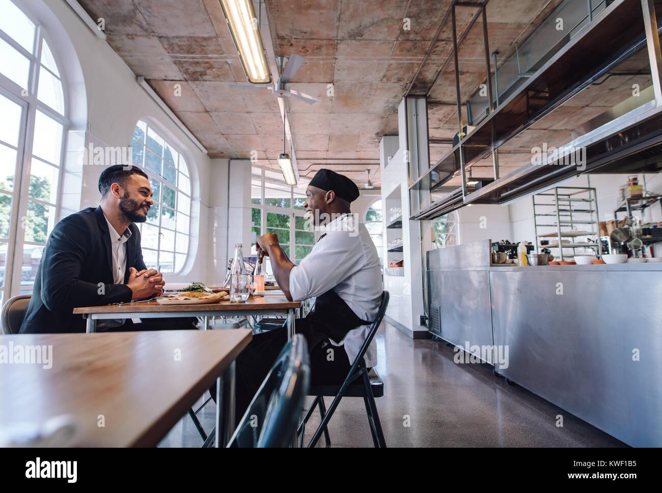 Restaurant Manager im Gespräch mit einem professionellen Koch. Cafe Inhaber und Koch sitzen an einem Tisch Stockbild