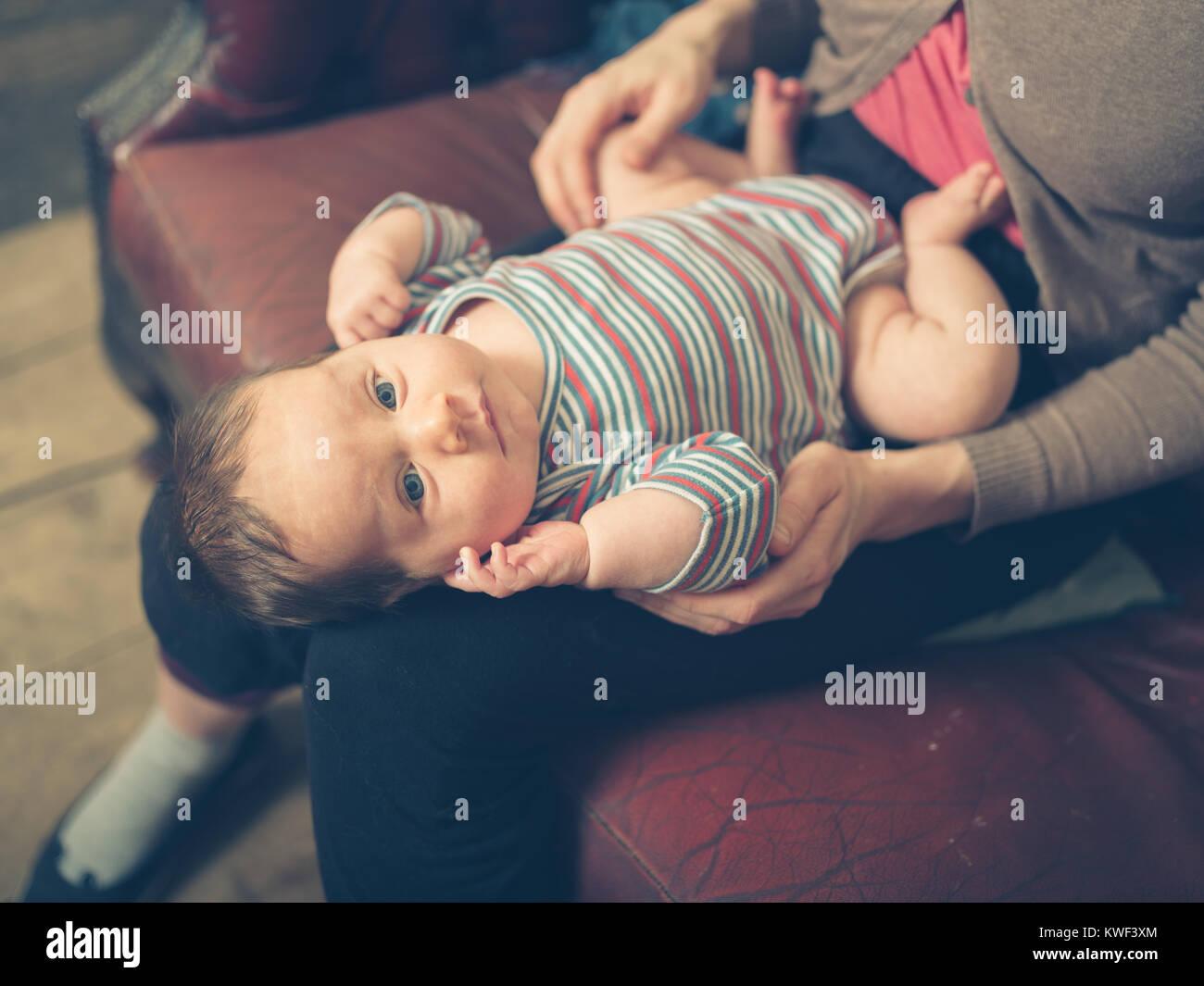 Ein glückliches Baby auf dem Schoß seiner Mutter zu Hause Stockbild