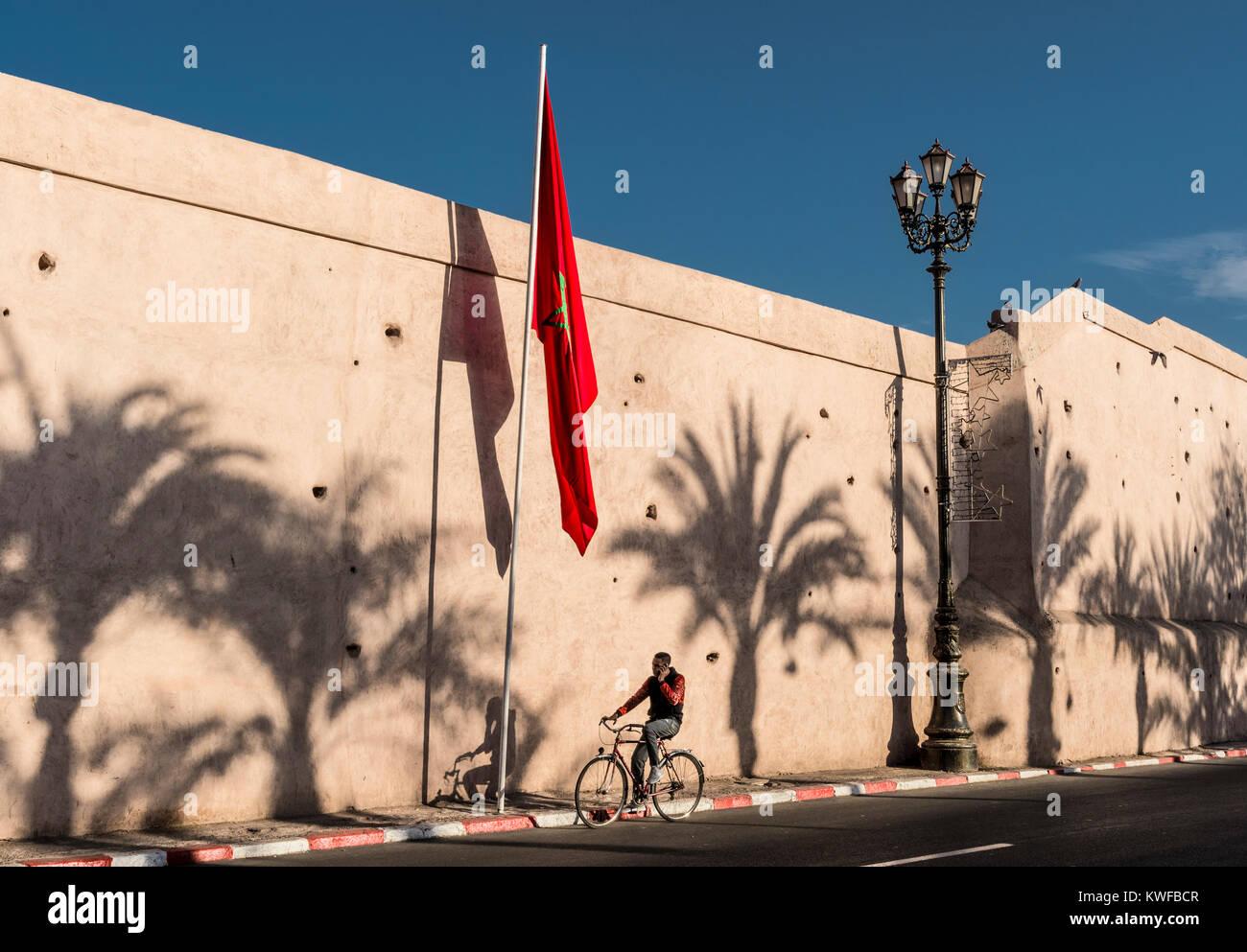 Marokkanische Flagge und Medina Stadtmauern mit Palmen Schatten. Stockbild