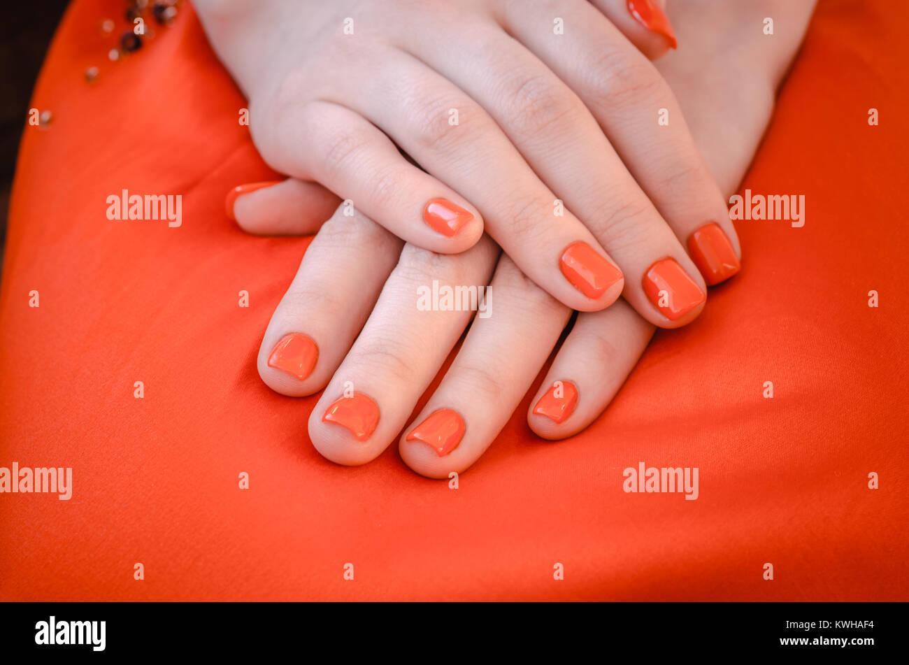 weibliche hände mit roten nägeln auf hintergrund rotes kleid