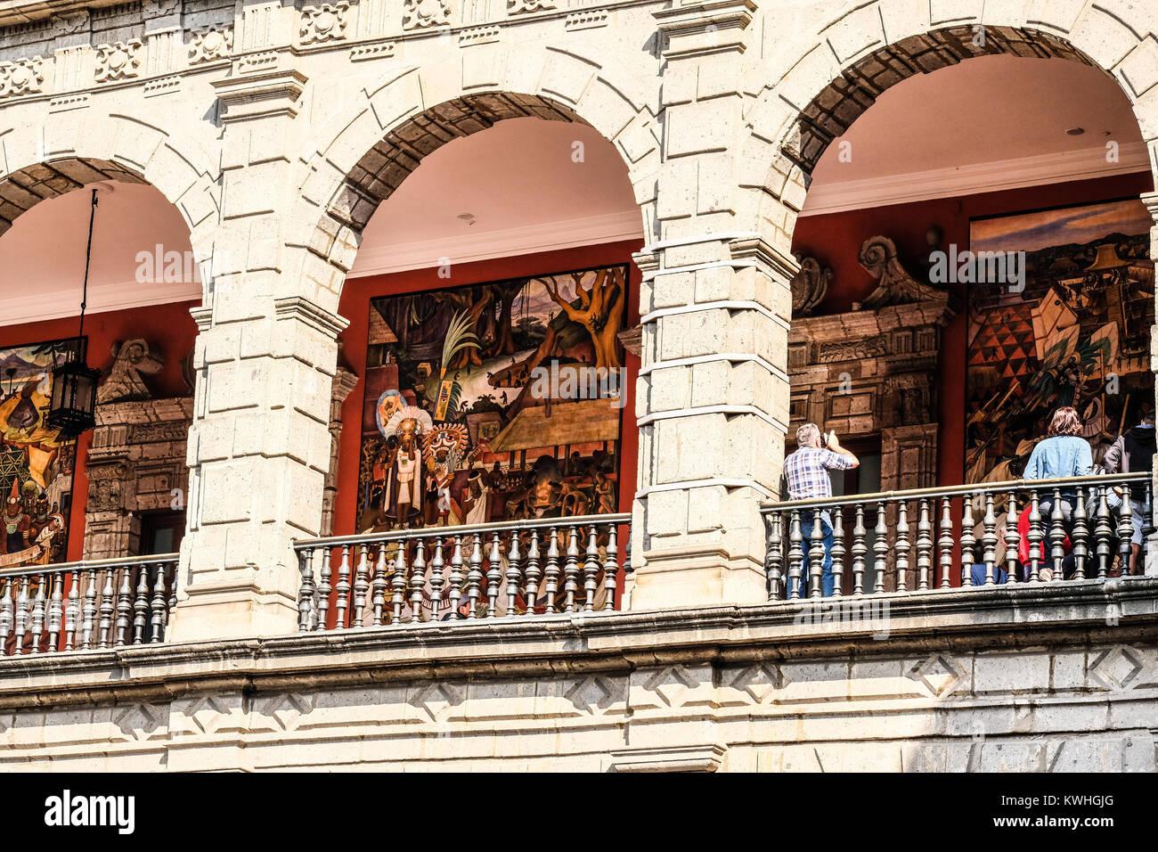 Touristen Anzeigen von Diego Rivera's Wandgemälde an der Mexico Plaza de la Consitucion Stockbild