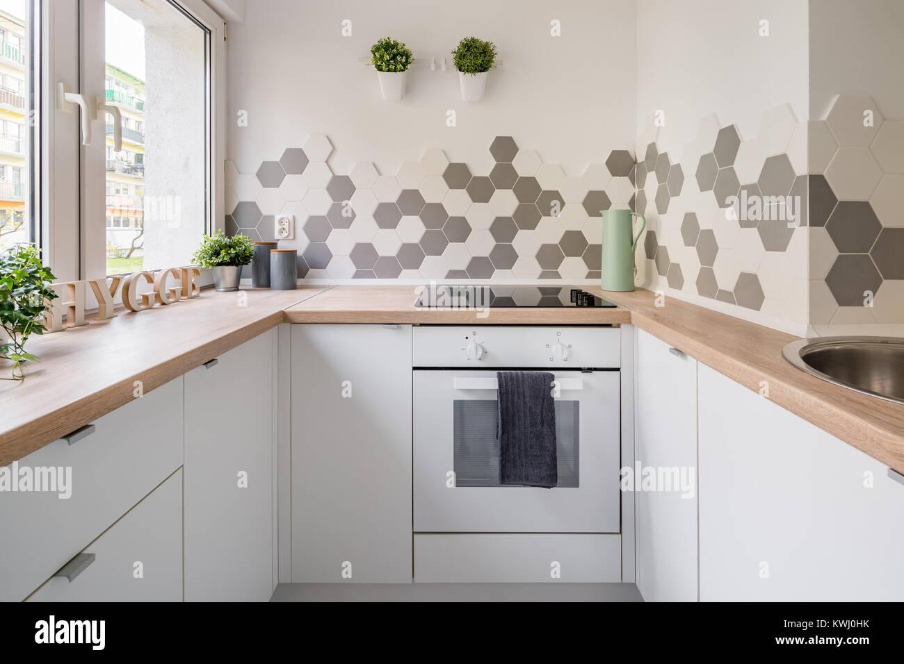 Weiß hygge Küche mit sechseckige Fliesen, Holz- Arbeitsplatte und ...