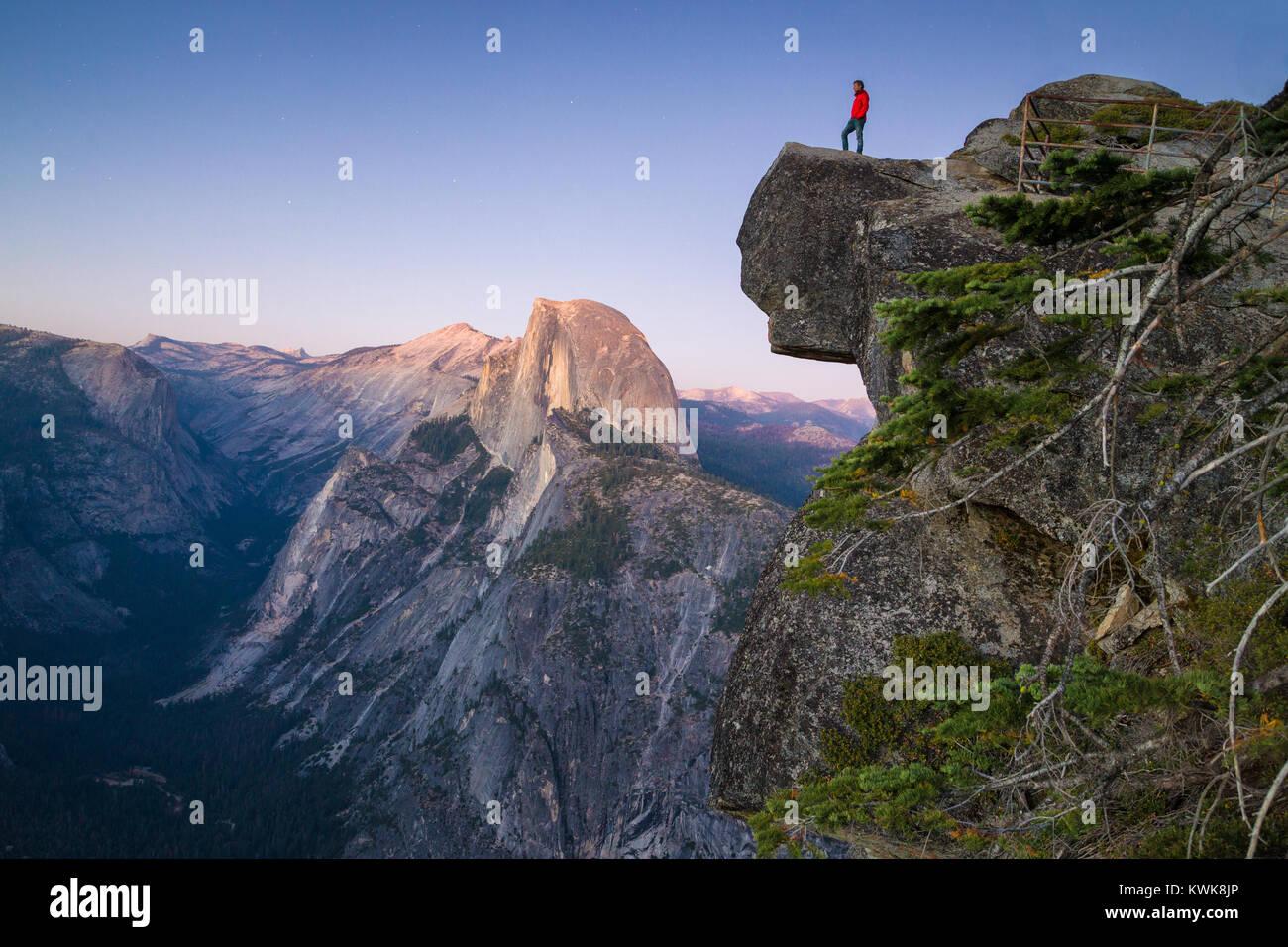 Eine furchtlose Wanderer steht auf einem überhängenden Felsen zur berühmten Half Dome am Glacier Stockbild