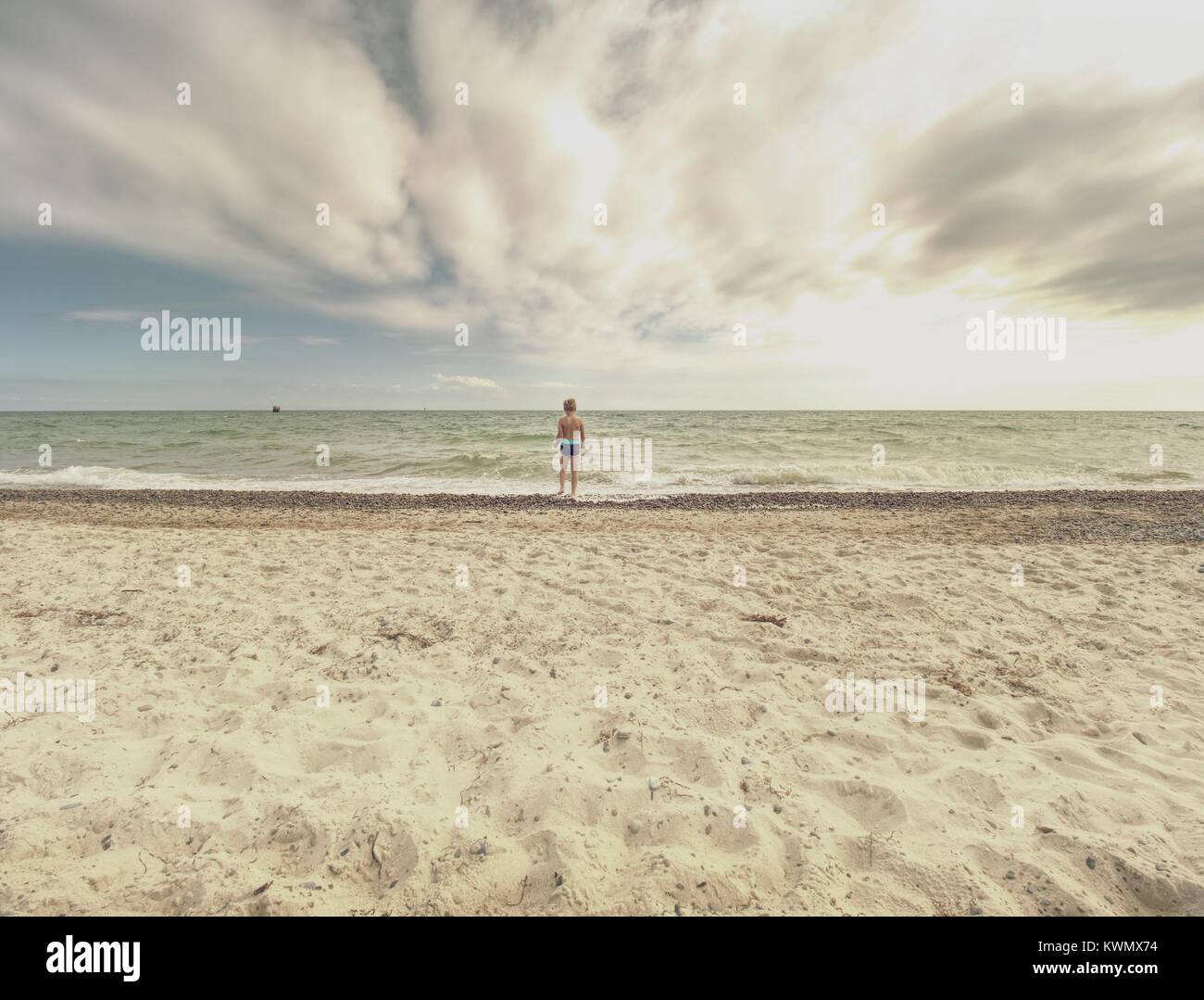 Blonde Haare junge Aufenthalt im kalten Meer tide. Kid auf steinigen Strand mit schäumenden Wellen. Windigen Stockbild