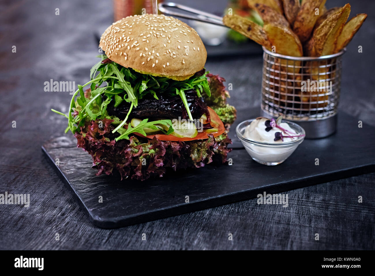Burger, Pommes mit Salat auf einem Tisch. Stockbild