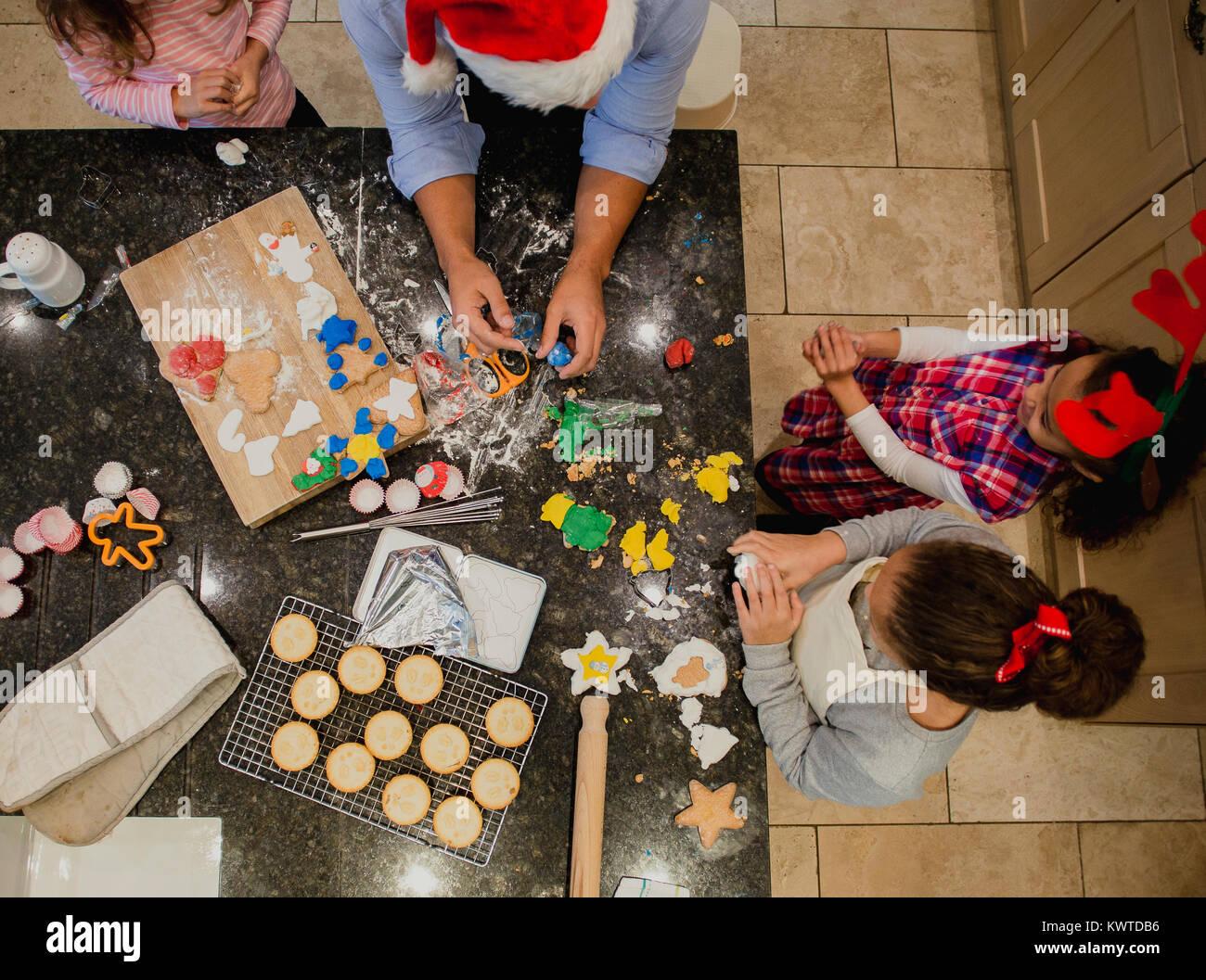 Luftaufnahme von einem Vater zu Weihnachten Kekse mit seinen drei Töchtern in der Küche ihres Hauses. Stockbild
