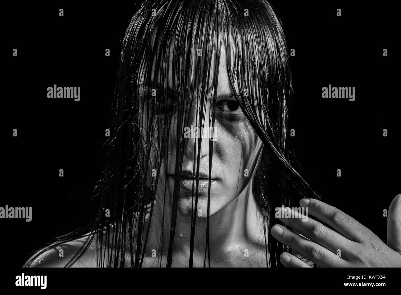 Ernsthafte wütende Frau mit nassen, schwarzen Haaren auf Kamera, Monochrom Stockbild