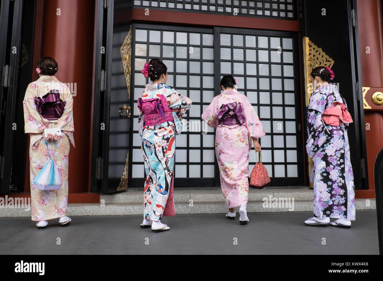 Japan, Tokio, Insel Honshu: Touristen, die traditionelle japanische Kleidung, hier vor einer Tür des Senso Stockbild