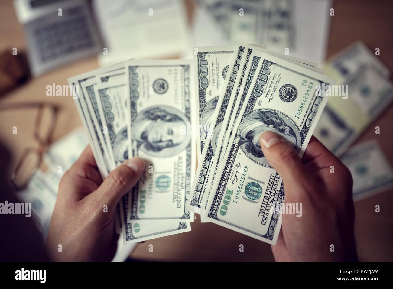 Business Mann zählen Einsparungen oder Bezahlung Geld mit Taschenrechner Stockfoto
