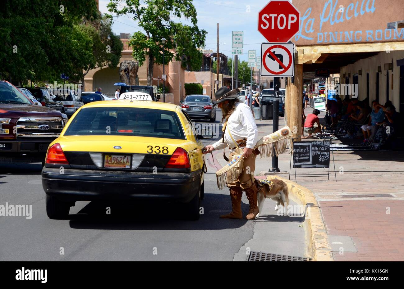 Old West Re-enactment Cowboy nimmt ein Taxi mit seinem Hund in Albuquerque, New Mexico Stockbild