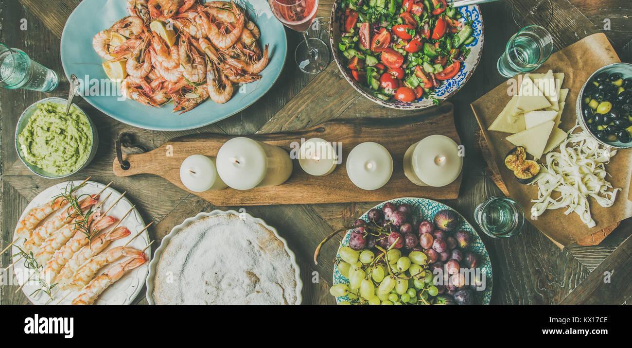 Flachbild-lay von Salat, Garnelen, Oliven-, Traubenkern, Kuchen, breiten Zusammensetzung Stockbild