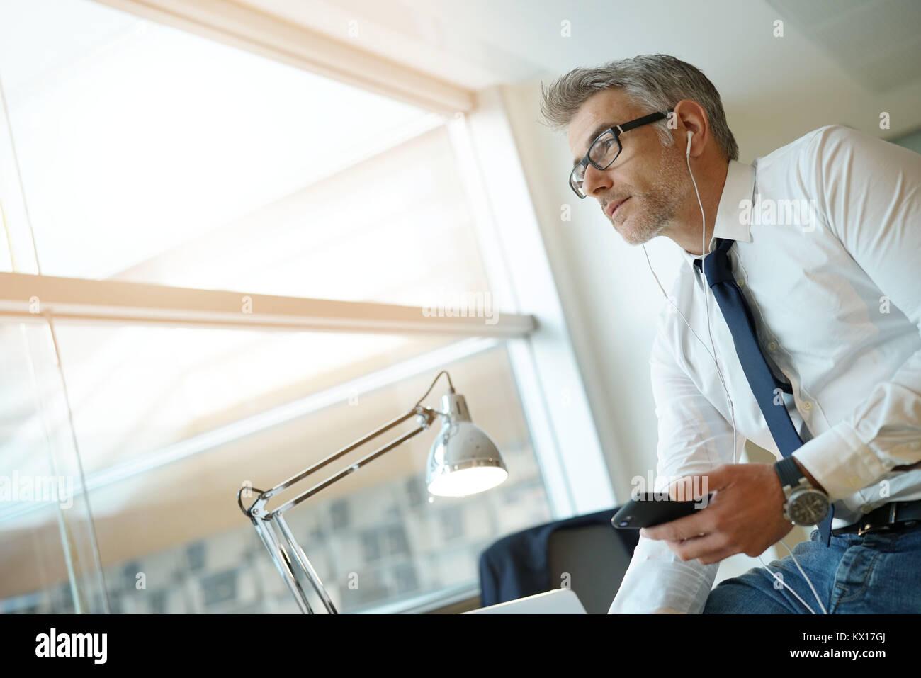 Geschäftsmann am Telefon sprechen in Büro, sitzen auf den Schreibtisch Stockbild