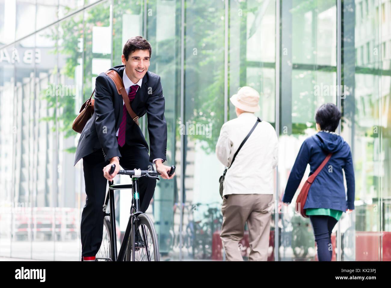 Fröhlicher junger Mitarbeiter reiten ein Dienstprogramm Fahrrad in Berlin Stockbild
