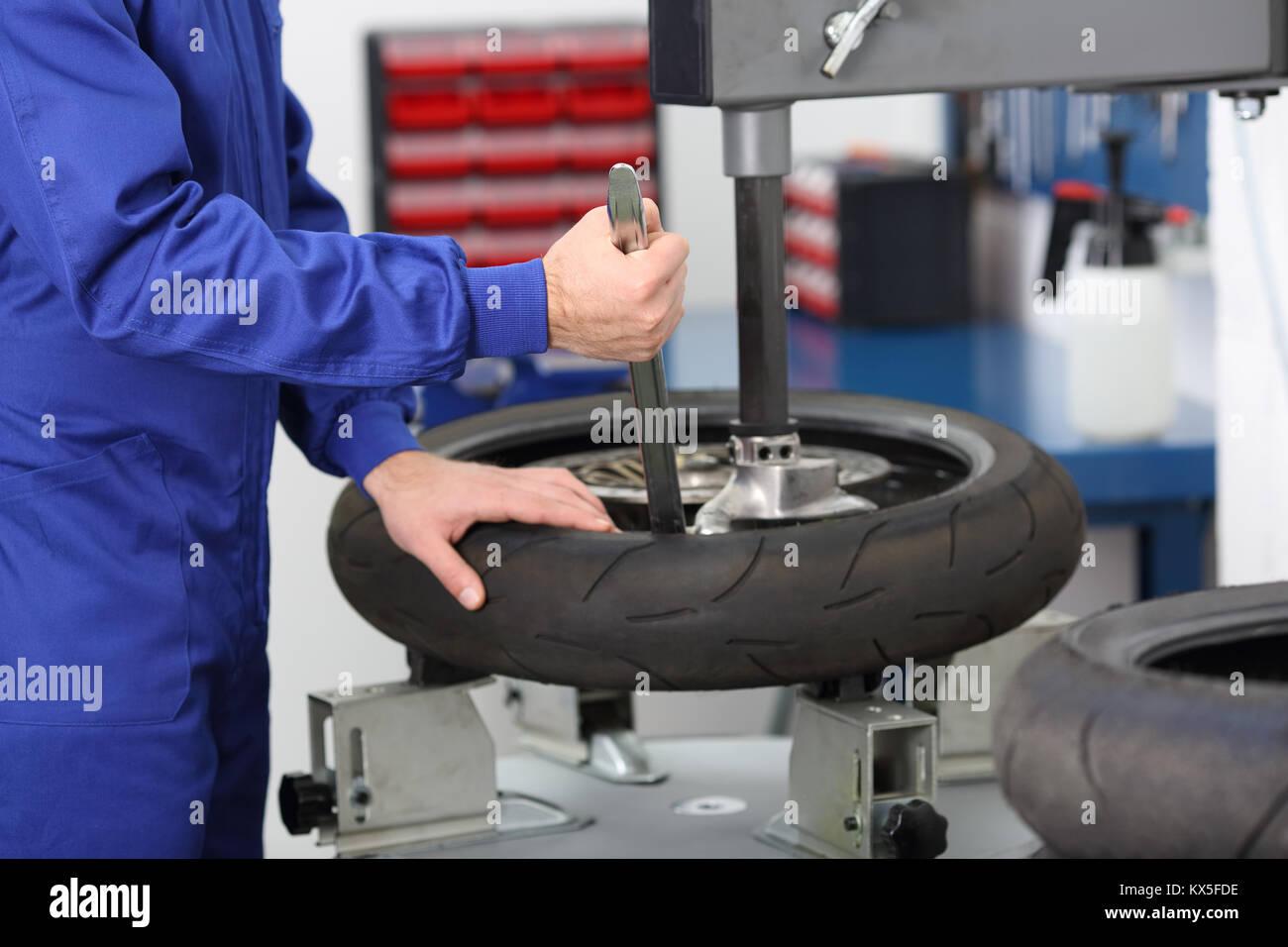 Motorrad Mechaniker Demontage eines alten Reifen in einer mechanischen Werkstatt Stockbild