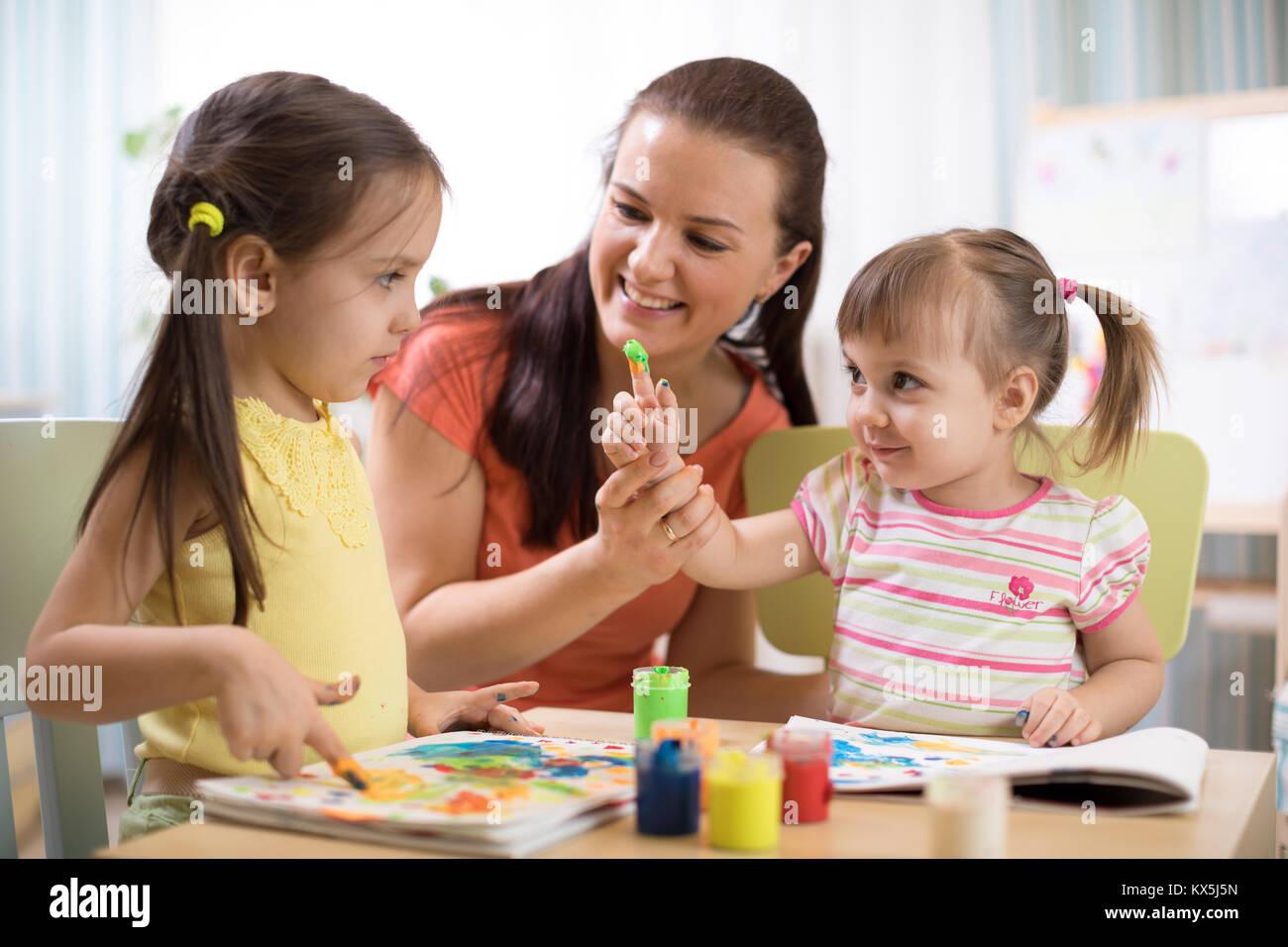 Kinder mit junge Lehrerin Frau zusammen Malen auf Tabelle im ...
