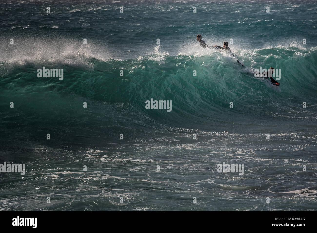 Drei junge Männer in Neoprenanzügen, stand Surfbrettern kämpfen gegen die Welle an der Küste Stockbild