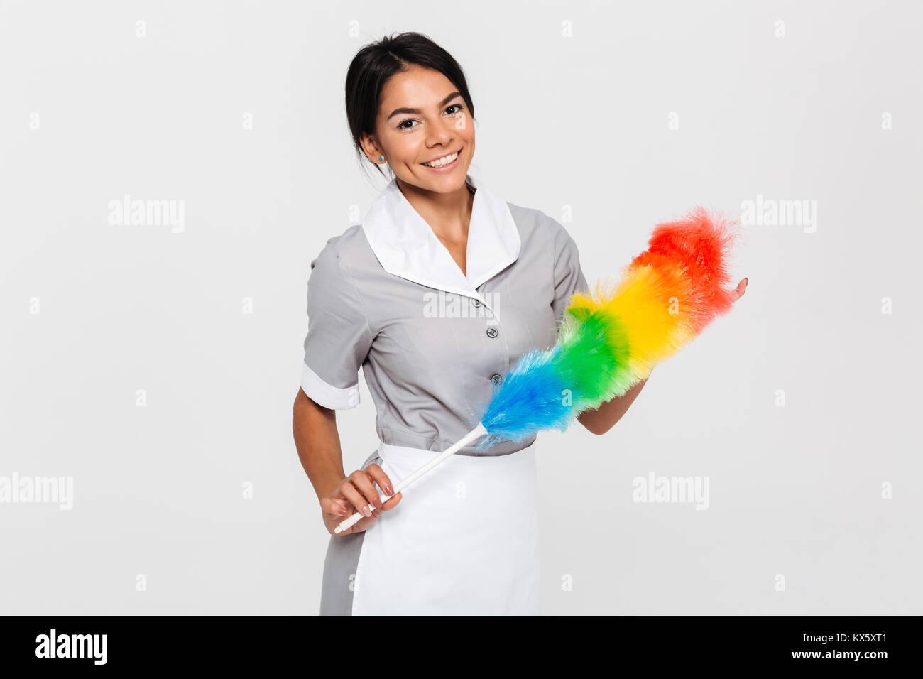 Fröhliche brunette Haushälterin in Uniform Holding bunte Duster und Kamera, auf weißem Hintergrund Stockfoto
