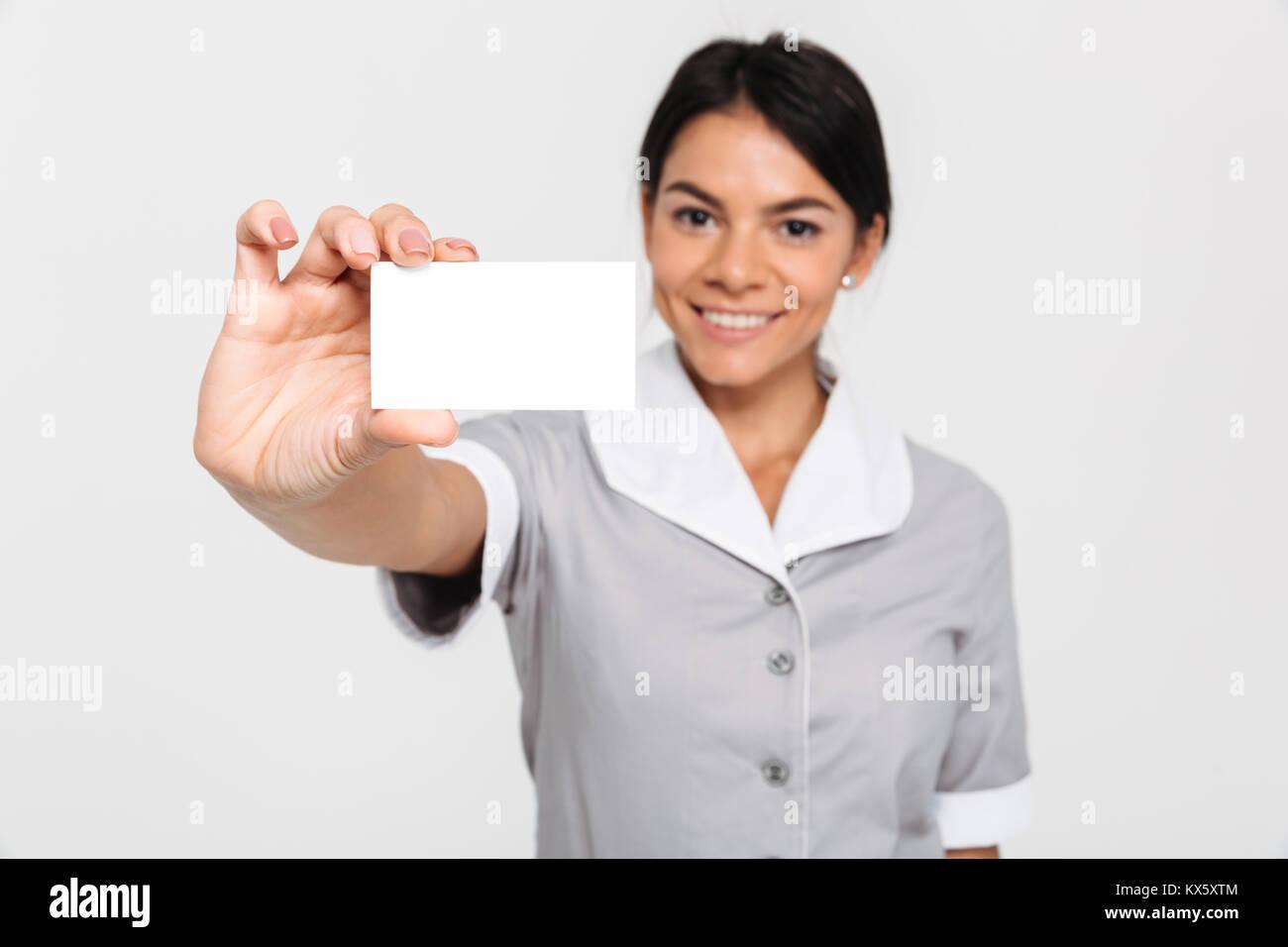 Junge attraktive femmale Haushälterin in Uniform zeigt leere Cutaway, selektiver Fokus auf Karte Stockfoto
