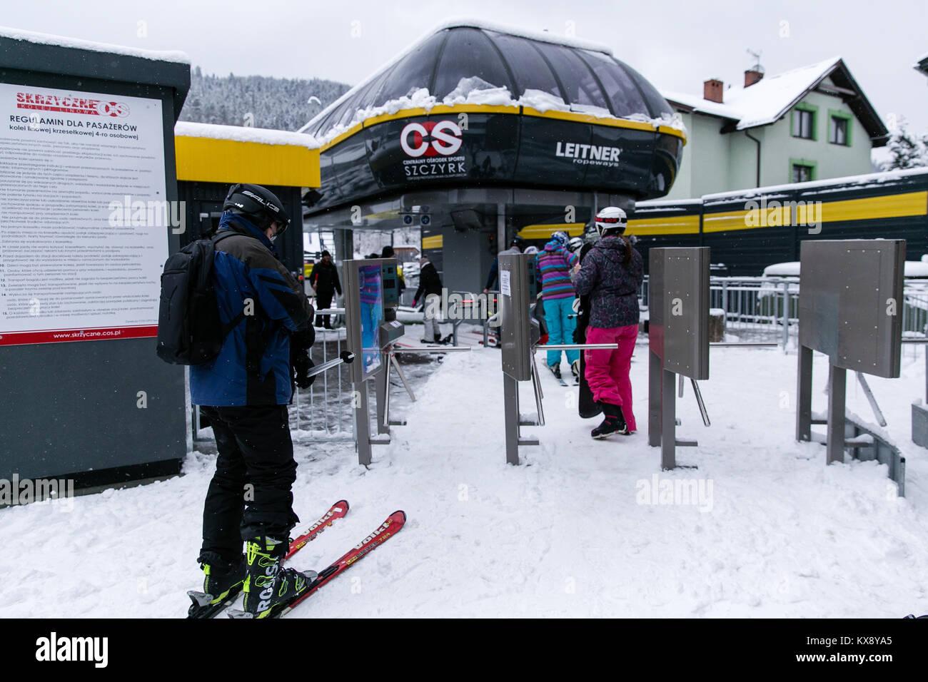 Skifahrer und Snowboarder gehen durch Drehsperren Tore und Boarding Sessellift auf dem Weg zum Gipfel des Berges in Szczyrk Polen Skrzyczne Stockfoto