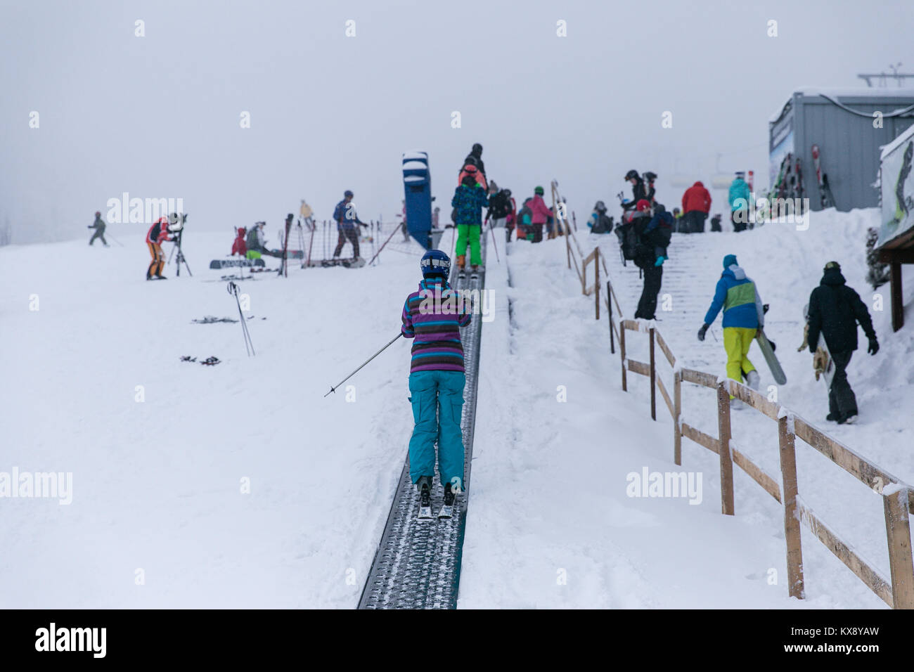 Skifahrer auf einem Band Skilift auf dem Weg in die zweite Etappe der Sessellift bringt Touristen auf den Gipfel des Berges in Szczyrk Skrzyczne, Polen Stockfoto