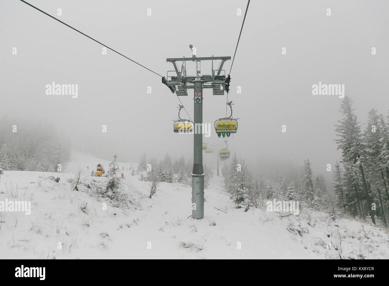 Ski Sessellift bringt Skifahrer und Snowboarder auf den Berg Skrzyczne nach starker Schneefall auf einem nebligen Stockfoto