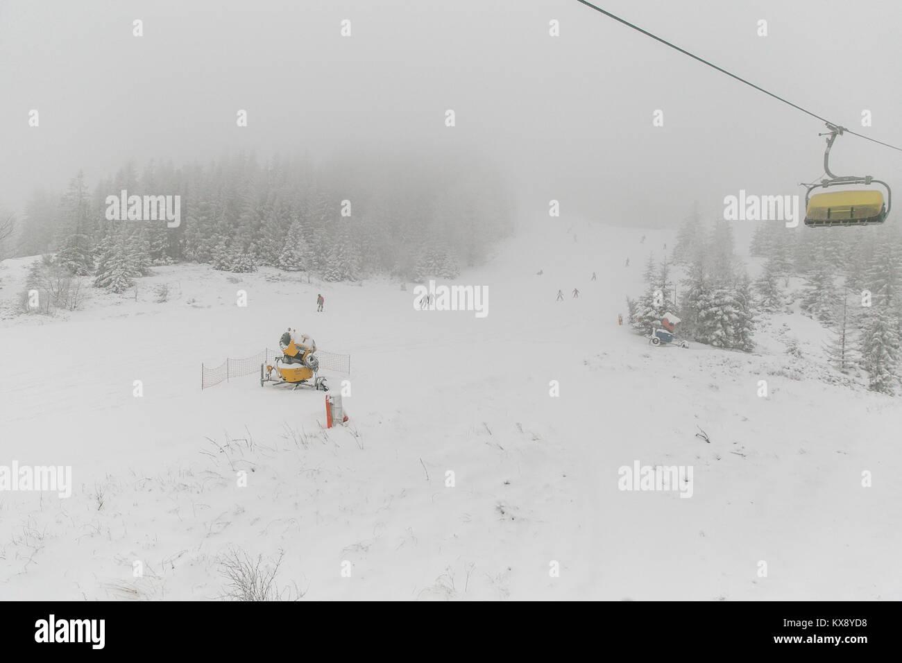 Menschen Skifahren und Snowboarden auf den Berg Skrzyczne nach starker Schneefall auf einem nebligen Wintertag in Szczyrk ski resort in Polen Stockfoto