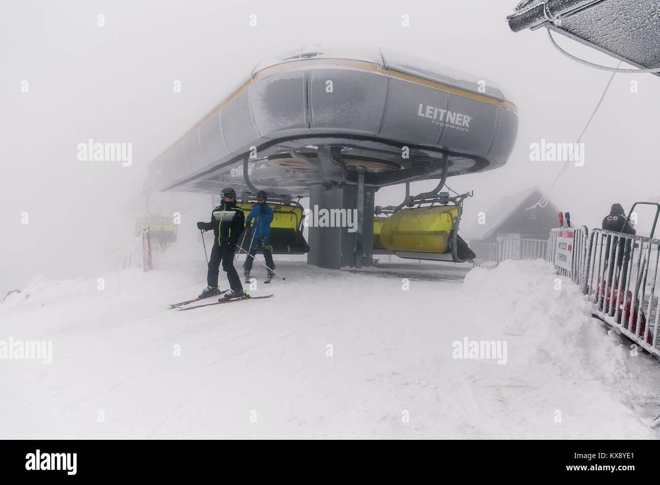 Skifahrer, der Sesselbahn auf dem Gipfel Der Berg Skrzyczne in Schnee auf einem nebligen Wintertag in Szczyrk ski resort in Polen Stockfoto