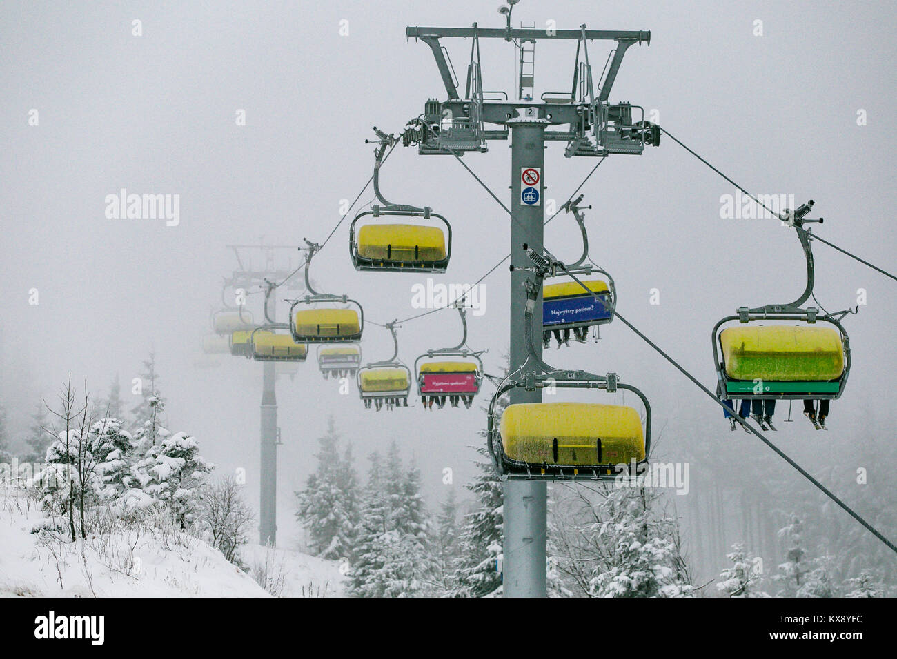 Ski Sessellift bringt Skifahrer und Snowboarder auf den Berg Skrzyczne nach starker Schneefall auf einem nebligen Wintertag in Szczyrk ski resort in Polen Stockfoto