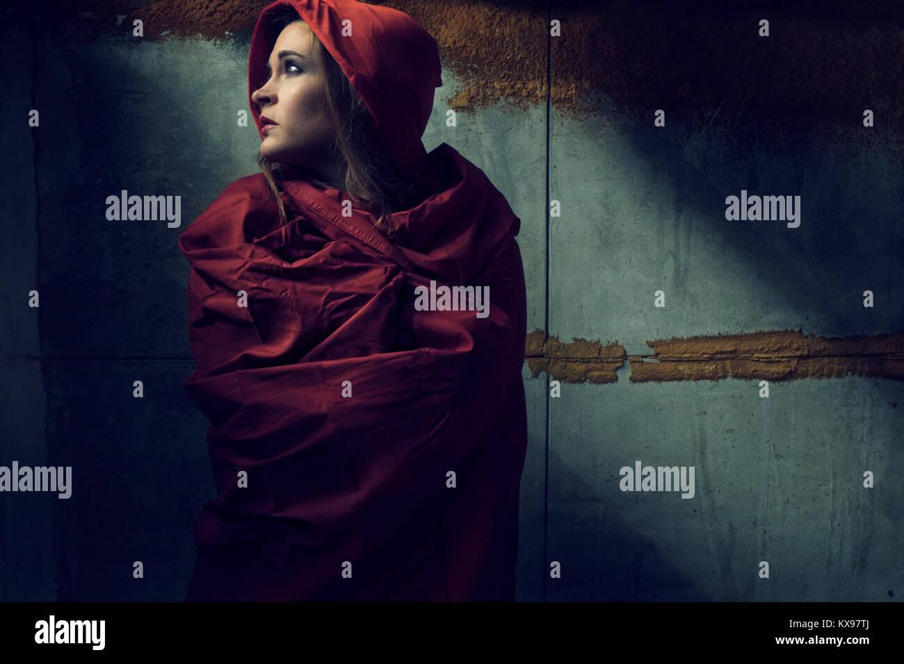 Junge Frau in rotem Umhang und Kapuze gewickelt Stockbild