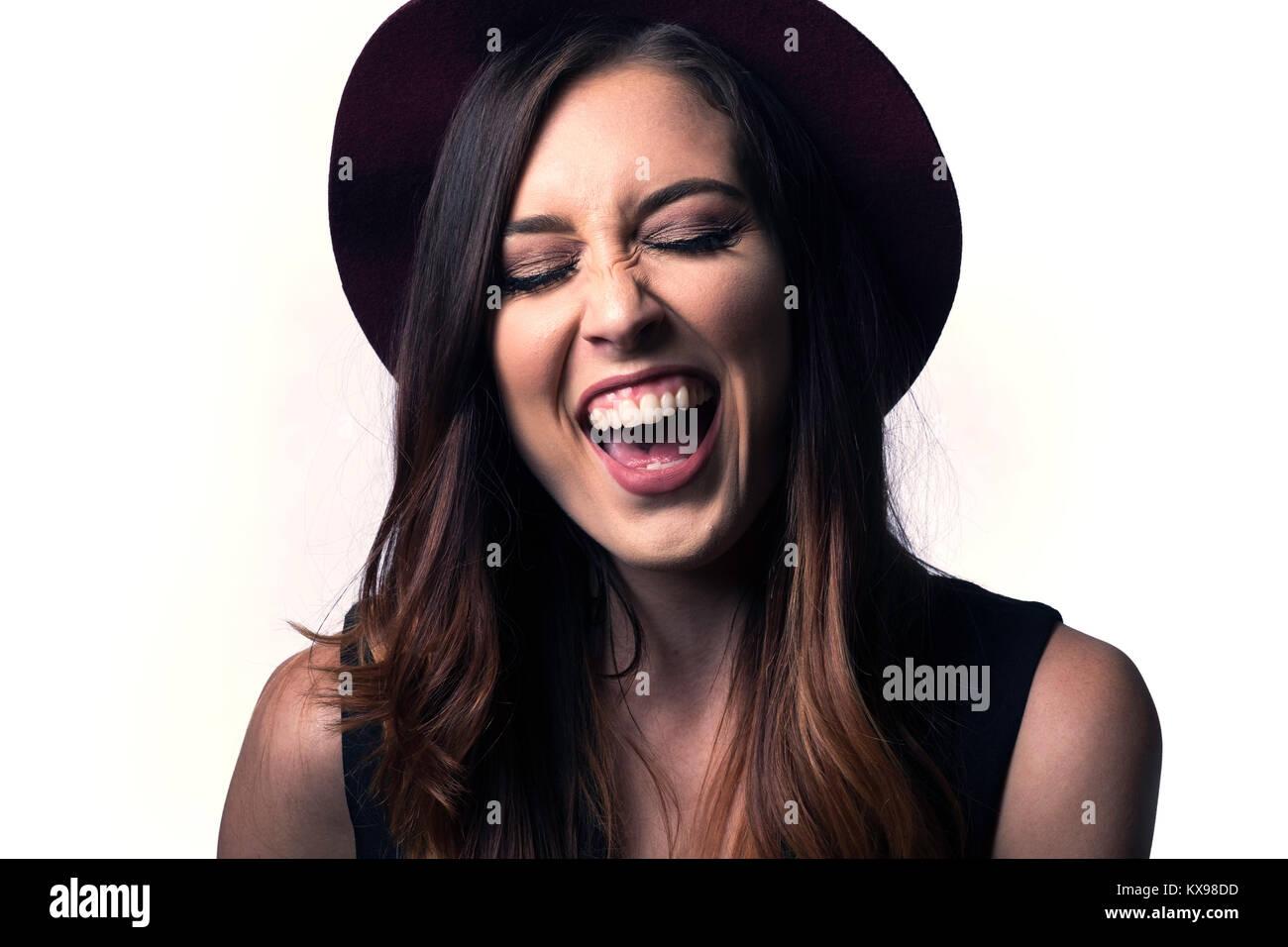 Junge Frau in hat Lachen spielen auf weißem Hintergrund Stockfoto