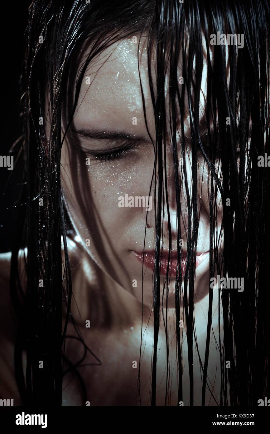 Ernste traurige Frau mit nassen, schwarzen Haar schließen ihre Augen in der Dunkelheit Stockbild