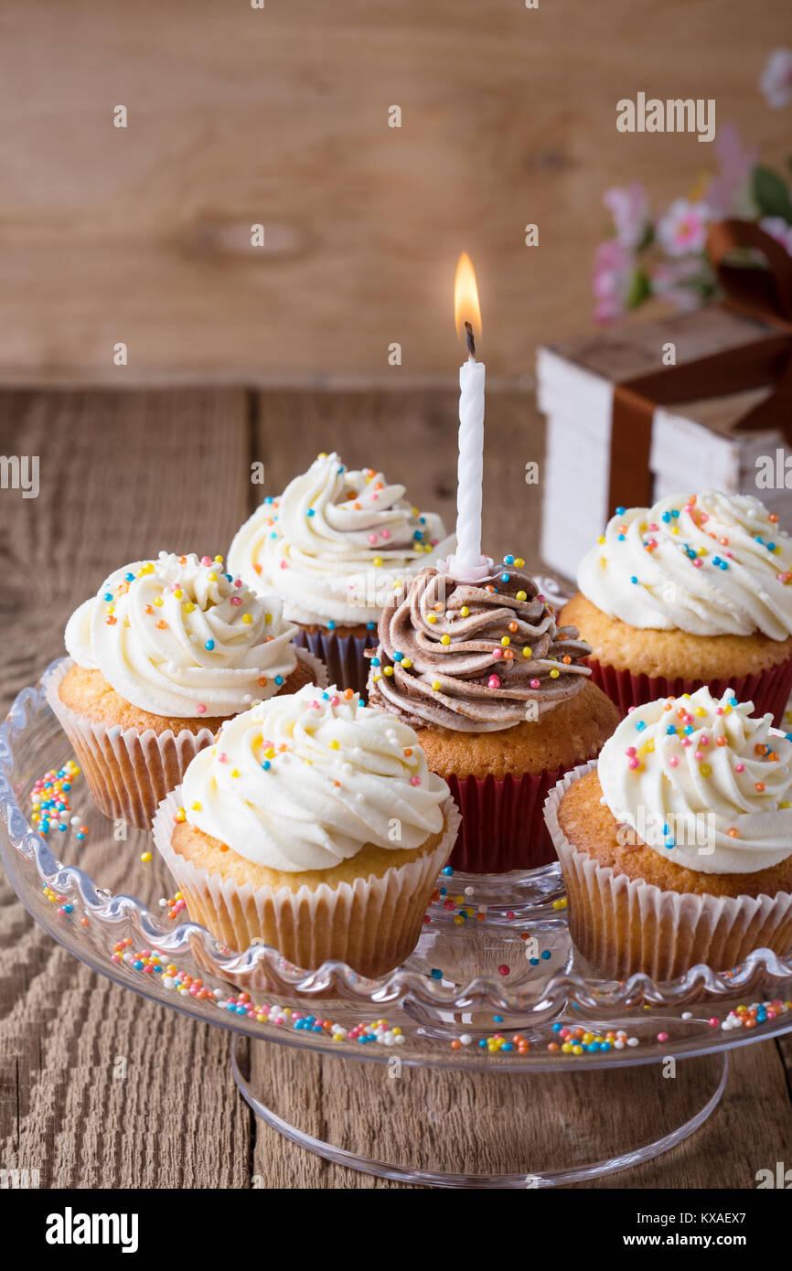 Lecker geburtstag Cupcakes mit einer Kerze serviert auf Glas cakestand auf festliche Holztisch Stockbild