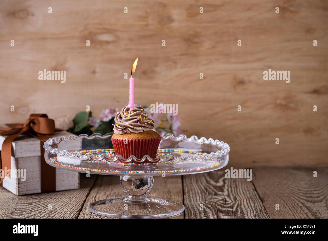 Lecker Geburtstag Kuchen mit einer Kerze serviert auf Glas cakestand auf festliche Holztisch Stockbild