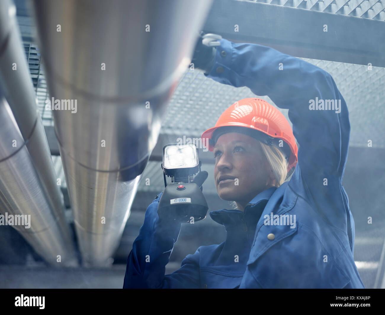 Techniker, Monteur mit orange Helm und Lampe kontrolliert Pipelines, Wattens, Tirol, Österreich Stockbild