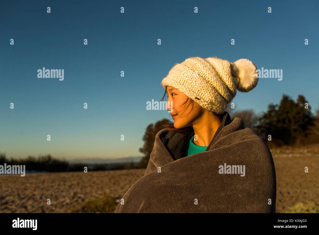 Junge Frau sitzend in gestrickt hat und in der Decke eingewickelt, während nach in Discovery Park, Seattle, Washington Stockfoto