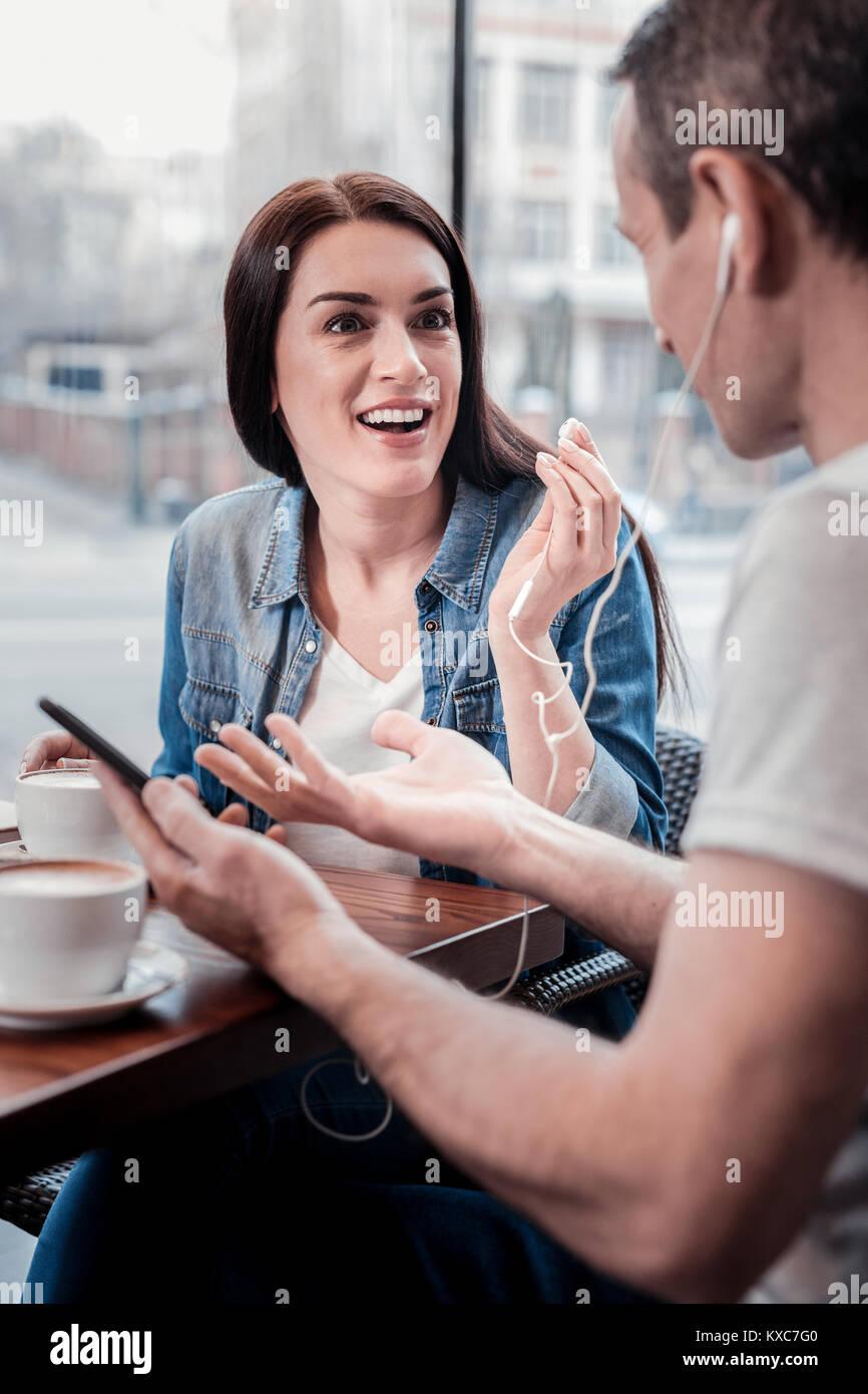 Fröhliche Frau erzählen Witz zu Ihrem Freund Stockbild