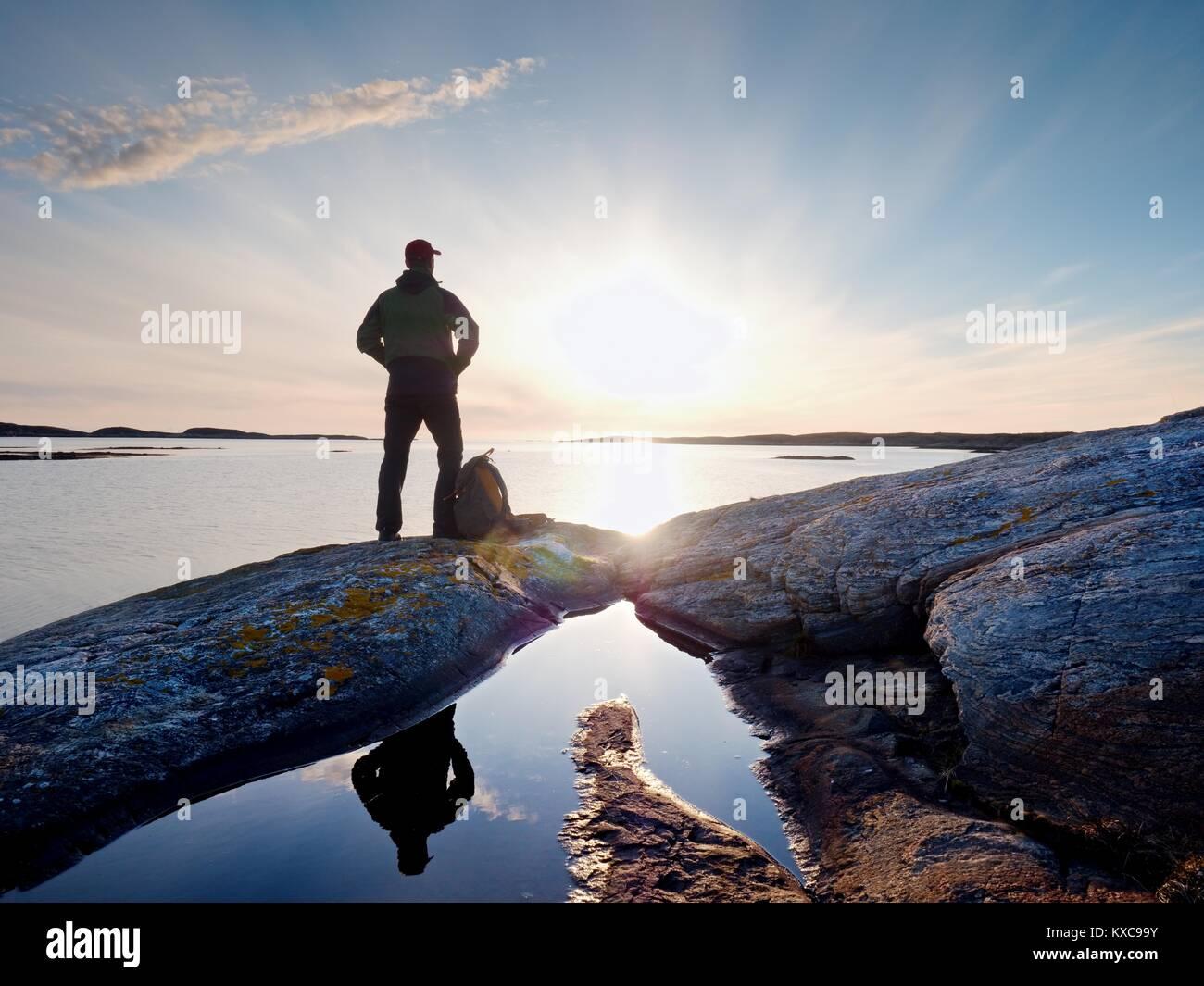 Junge stehende Mann mit Rucksack. Wanderer auf dem Stein am Meer an bunten Sonnenuntergang Himmel. Schöne Landschaft Stockbild