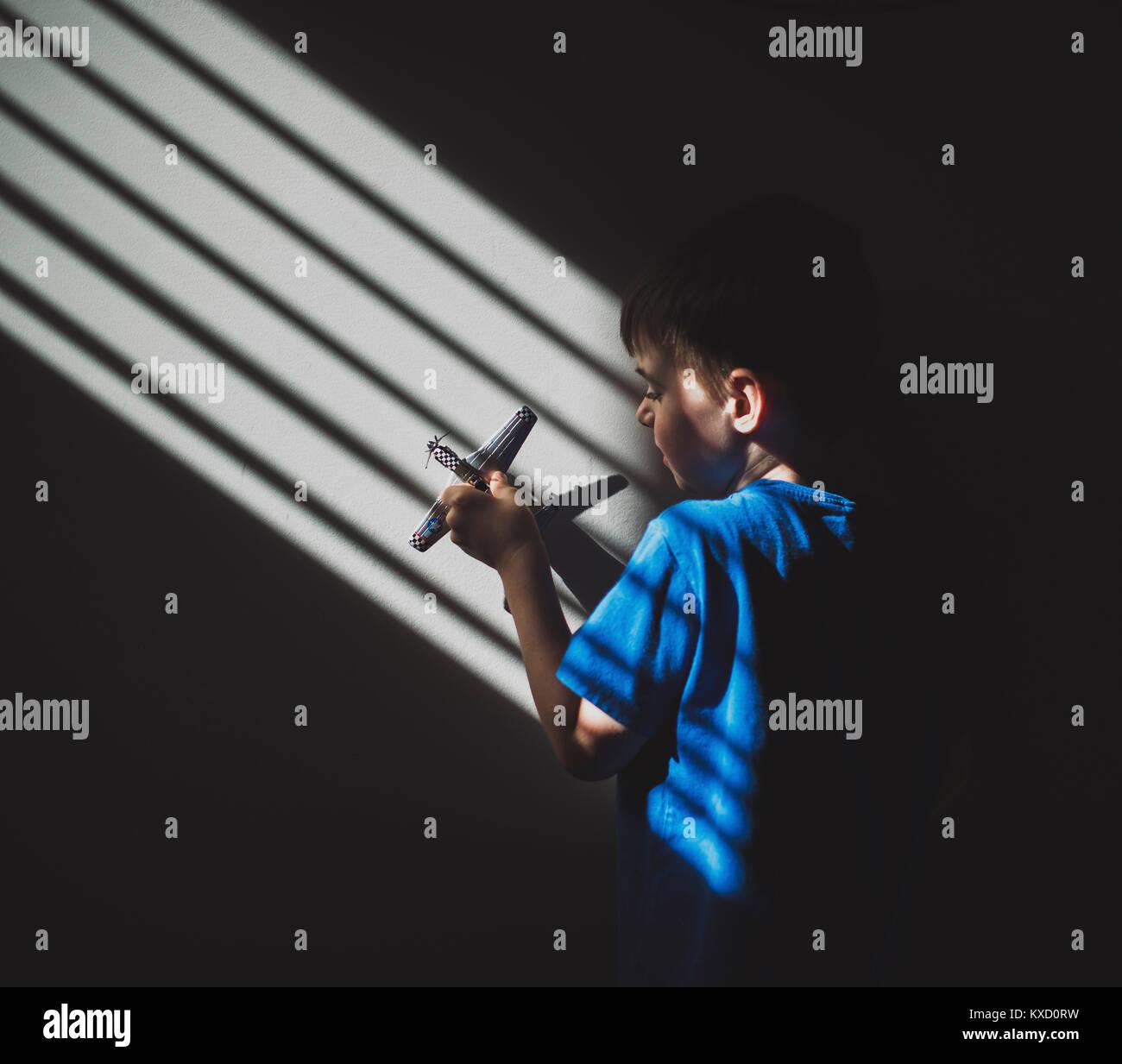 Sonnenlicht fällt auf Jungen spielen mit Spielzeug Flugzeug auf Wand in der Dunkelkammer Stockbild